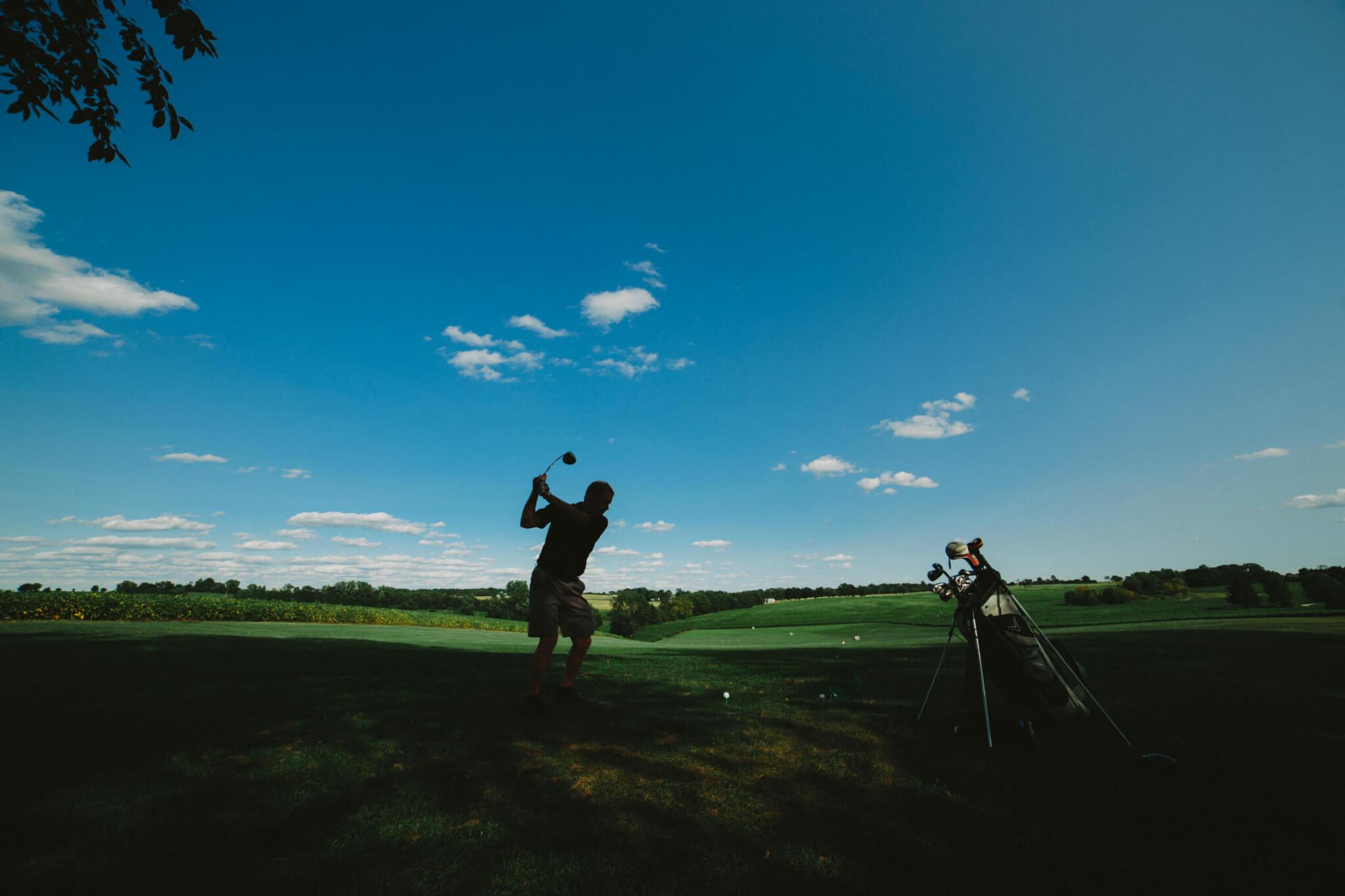 Golfer in shadows tees off